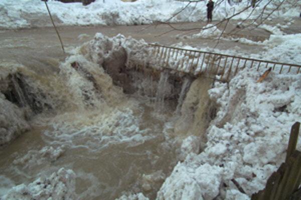 Ľad a sneh zapchali korytá potokov a voda sa valila po ceste.