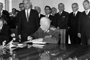 Prezident Ludvík Svoboda podpisuje ústavný zákon o federácii na Bratislavskom hrade, vpravo A. Dubček, druhý sprava podpredseda československej vlády Gustáv Husák.