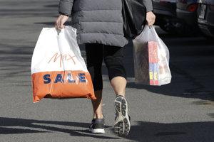 Žena nesie nákup v plastových taškách.