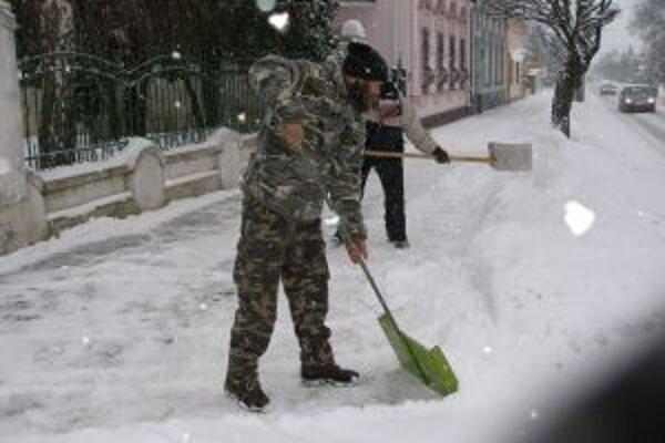 Bezdomovci sa zohriali aj pri odpratávaní snehu pred Domom Červeného kríža.
