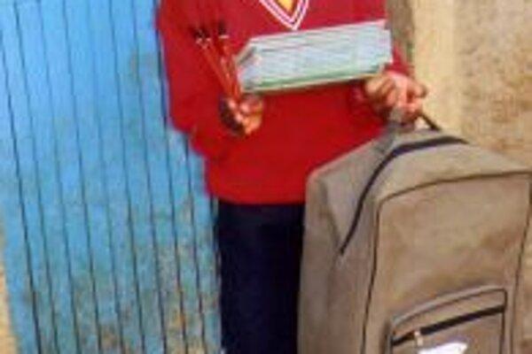 Christine Kalunda v novom úbore na telesnú výchovu. V náručí drží učebnice, školskú tašku a školskú pomôcku.