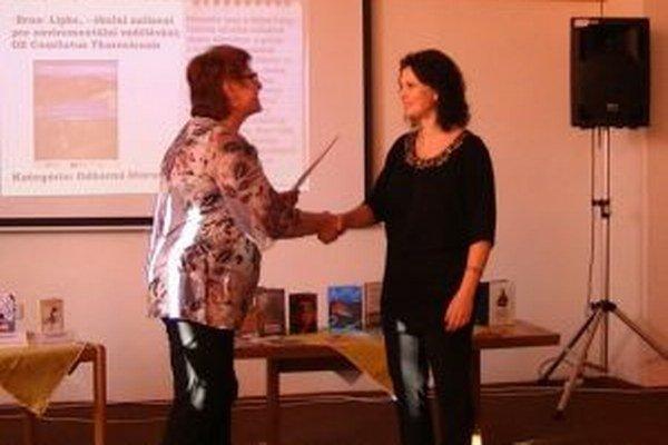 Lucia Jesenská (vpravo) preberá za Blažeja Beláka a jeho knihu Príbehy a povesti z Turca cenu z prvé miesto od riaditeľky Turčianskej knižnice Kataríny Vandlíkovej.