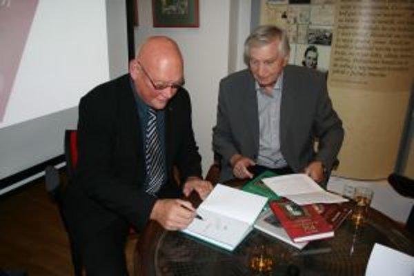 Marián Tkáč (vľavo) podpisuje svoje knihy.