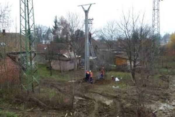 Stĺp, ktorý montujú elektrikári je približnou hranicou pozemku dotknutej rodiny.