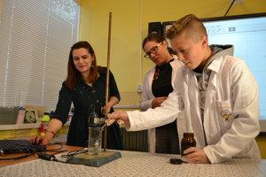 Učiteľky chémie a biológie Lenka Jeňová a Zdenka Bendová (v bielom plášti) s ôsmakom Martinom Vaceľom počas chemického pokusu.