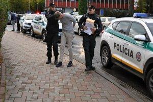 Vodič Mercedesu v sprievode policajtov, vzadu stojí vodič Ferari.