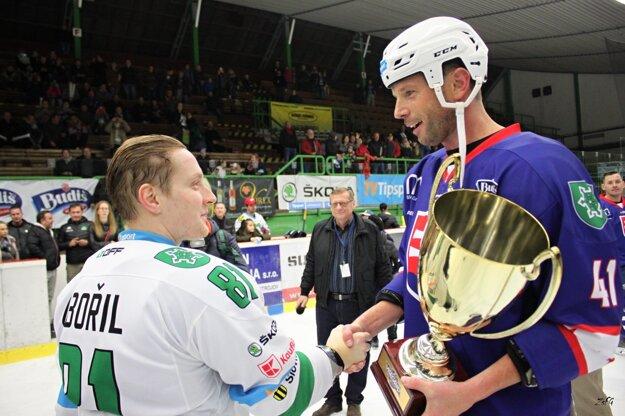 Vyšehradský pohár si z rúk Richarda Lintnera preberá kapitán MHC Nové Zámky Adam Zbořil.