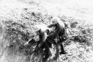 Kanadský vojak pomáha zranenému nemeckému vojakovi.