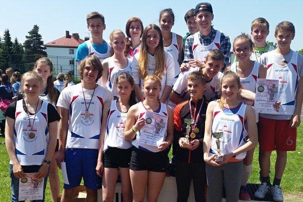 Mladí atléti s trofejami.