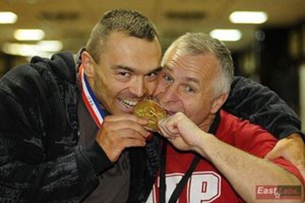 Ľuboš Maliňák na fotografii vľavo testuje pravosť zlatej medaile spoločne s trénerom Ľubomírom Hečkom.