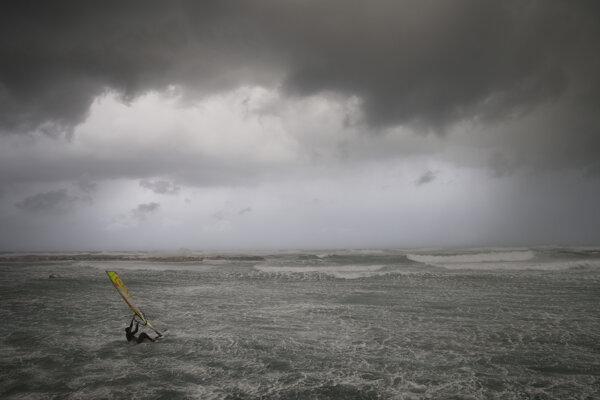 Surfista uprostred búrky na pobreží izraelského mesta Tel Aviv.