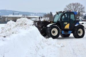 Nakladač odhŕňa snehové záveje na ceste pred obcou Novosad.