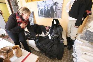 Starostka obce Dana Lóžiová ukazuje vzácne kúsky odevu na obecnej výstave.