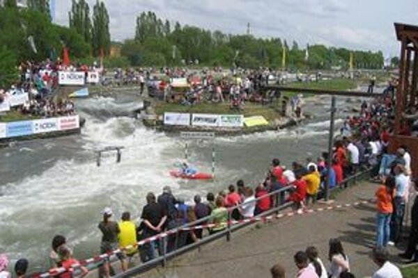 Výkony súťažiacich a rozbúrená voda priťahujú pozornosť divákov.