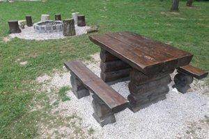 V blízkosti ohnísk sú aj stoly s lavicami.