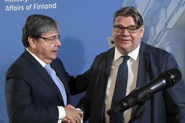 Fínsky minister zahraničných vecí Timo Soini, vpravo, si potriasa ruko s kolumbijským ministrom zahraničných vecí Carlosom Trujillom.