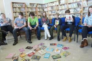 Deti hľadajú knihu, zktorej práve počuli úryvok.