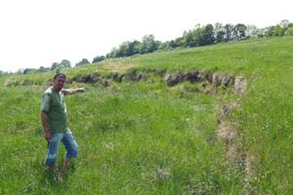 Starosta Štefan Benka ukazuje na svah, ktorý sa pohol a zem sa zastavila len pár metrov od domov.