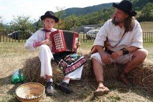 Chlapci sedeli na bale sena pri stánku s chlebom a hrali na heligonkách.