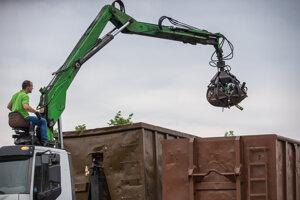 Pracovník skládky prenáša sklene fľaše a iný odpad zo skla