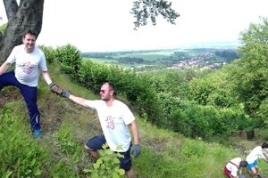 Dobrovoľníci v obci Podhradík vynášajú kameň na obnovu hradby.