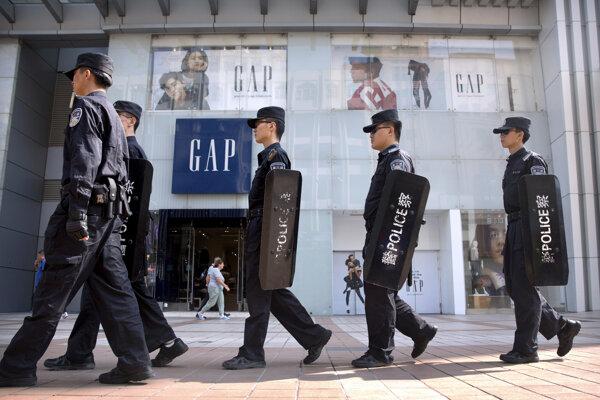 Čínski policajti hliadkujú pred obchodom americkej odevnej značky GAP v Pekingu.