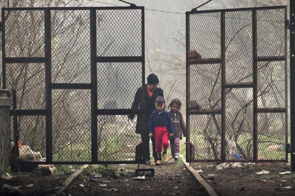 Matka s deťmi vstupuje do priestoru hangáru, v ktorom si migranti postavili stany.