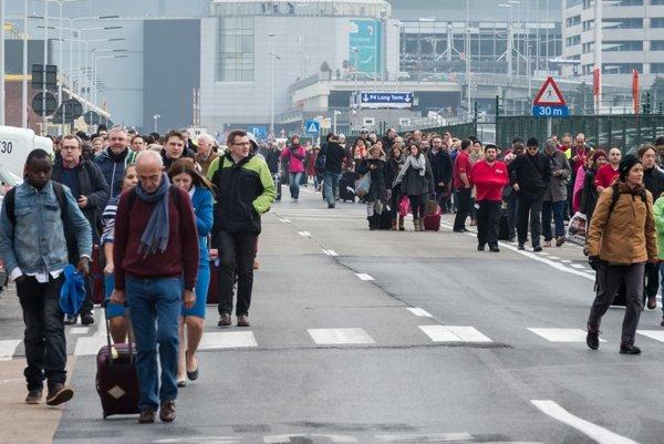 Ľudia odchádzajú z letiska po výbuchu.