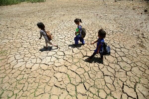 Deti sa vracajú zo školy kráčajúc po dne vyschnutého jazera v horúcom letnom dni a okraji indického mesta Džammú 30. mája 2019.