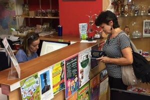 Prvá zákazníčka si kupuje prešovskú nulovú bankovku.