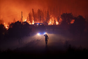 Člen pohotovostnej pracovnej jednotky pri hasení požiaru neďaleko dediny Cardigos v strednom Portugalsku v nedeľu 21. júna.