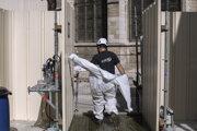 Jeden z pracovníkov pri obnove ktedrály Notre-Dame si oblieka ochranný odev.