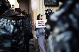 """Demonštrantka drží transparent s nápisom """"Vráťte nám naše voľby v Moskve""""."""