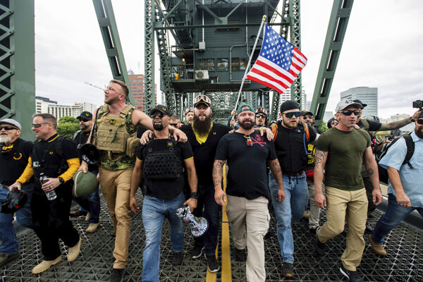 Stúpenci krajnej pravice kráčajú cez most  Hawthorne počas zhromaždenia  v Portlande 17. augusta 2019. Polícia pri zásahu zatkla najmenej 13 ľudí a zaistila kovové tyče a ďalšie zbrane.
