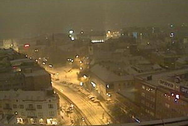Fotografia zo zasneženého Námestia SNP v Bratislave v nedeľu po ôsmej večer.