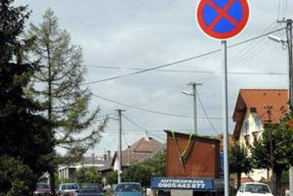 Zákaz zastavenia. Značenie osadené na jednom konci ulice robí z cesty takmer jednosmerku. Autá sa musia navzájom vyhýbať.