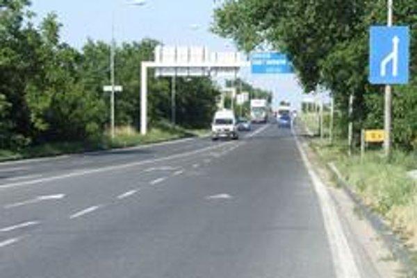 Jazdné pruhy sa spájajú v úzkom mieste. Dopravná značka informuje vodičov neskoro