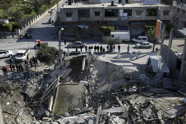 Palestínčania sa zhomažďujú pred zničenou viacposchodovou budovou po izraelskom leteckom útoku na Gazu.
