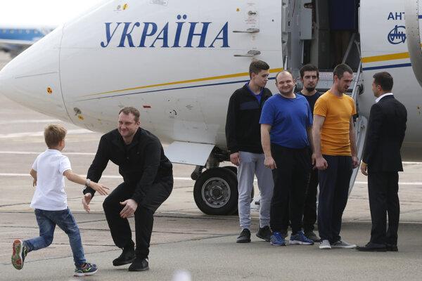 Prezident Ukrajiny Volodymyr Zelenskyj (vpravo) víta prepustených občanov Ukrajiny.