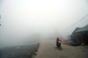 Muž ide na motorke v hustej hmle a dyme po lesných požiaroch v Palembangu na indonézskom ostrove Južná Sumatra 14. októbra 2019.