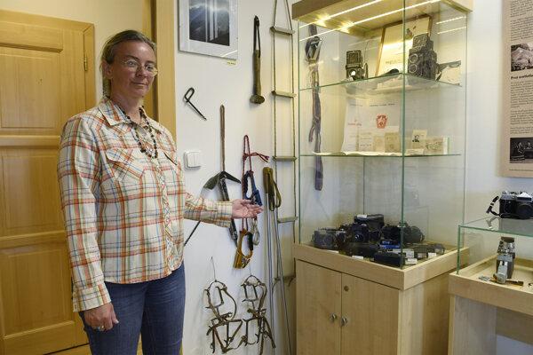 Riaditeľka múzea Ivana Figová ukazuje na dobovú horolezeckú výzbroj bývalého horolezca a filmára Juraja Weinczillera.