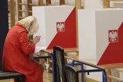 Poľská volička si pripravuje hlasovací lístok počas hlasovania v parlamentných voľbách vo volebnej miestnosti vo Varšave 13. októbra 2019.