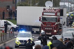 Policajné autá eskortujú nákladné auto, v ktorom našli 39 mŕtvych osôb v priemyselnom parku.