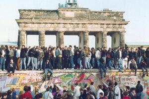 Na archívnej snímke z 10. novembra 1989 sa východní a západní Nemci zhromažďujú na Berlínskom múre pred Brandenburgskou bránou, deň po páde železnej opony.