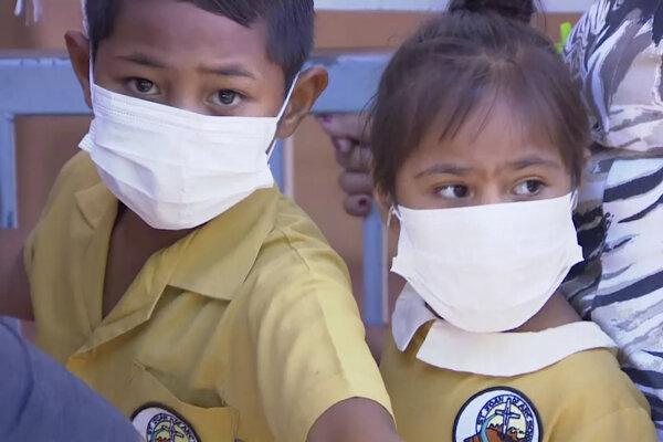 Deti majú na tvári rúško a čakajú na očkovanie v zdravotnom stredisku v Apii na Samoe.