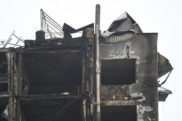 Úplne zničená strecha bytovky a poschodia pod ňou.