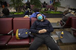 Cestujúci s maskou na medzinárodnom letisku v Pekingu.