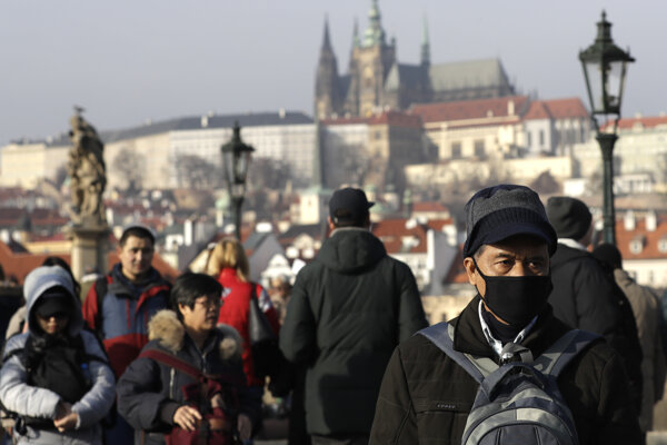 Turisti sa v centre Prahy rúškami.