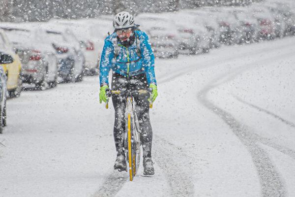 Cyklista ide po ceste počas sneženia v Bratislave.