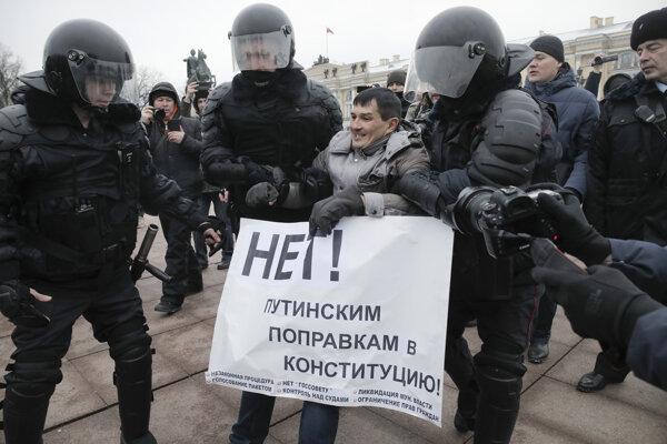 Členovia poriadkovej polície zadržujú demonštranta počas protestu proti zmenám ústavy navrhnutým prezidentom Vladimirom Putinom.